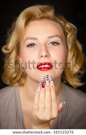 Pretty blond girl model like Marilyn Monroe like Marilyn Monroe with sensual red lips and long nails isolated on black background - stock photo