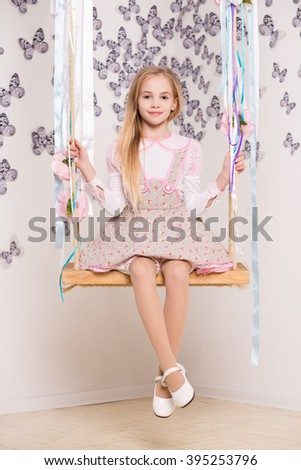 Pretty blond girl posing on the swing - stock photo