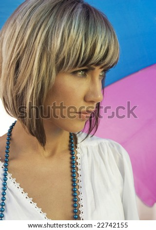 Pretty blond girl under summer umbrella - stock photo