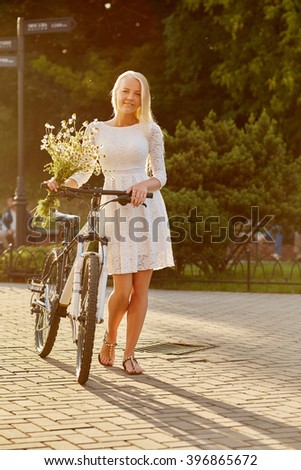 pretty blond girl with camomile bouquet with bike walking - stock photo