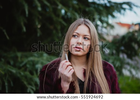 Pretty blond girl with long hair smoking in the park