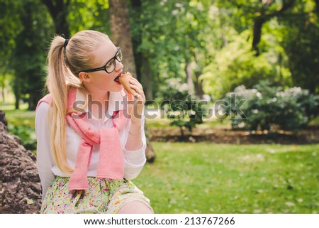 Pretty blond girl with long ponytail seating in park and eating ice cream. Selective focus.  - stock photo