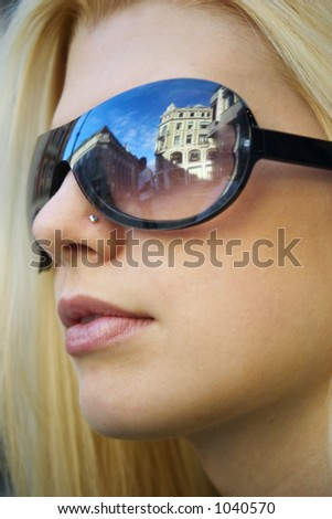 Pretty blond girl with sunglasses and the blue sky reflection - stock photo