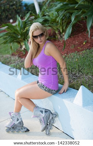 Pretty blond haired model on in line skates.