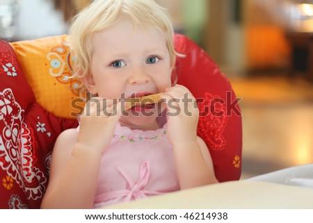 pretty blond little girl eats bread, sitting in an armchair - stock photo