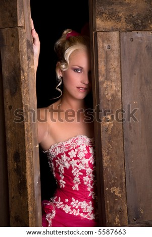 Pretty blond peering out from between the barn doors - stock photo