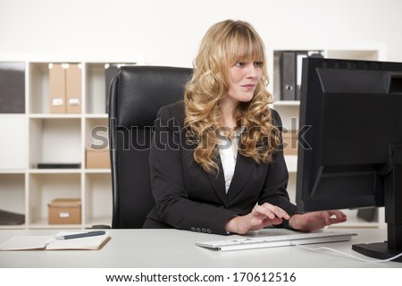 Pretty blond secretary or personal assistant working at her desk in the office typing on her desktop computer