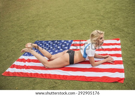 Pretty blond sexy girl in bikini lying on the American flag on green grass meadow or field , view from above Cut blondy woman with sexual barefoot legs look at camera Empty space for inscription