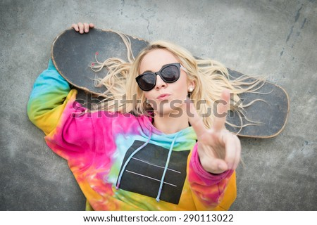 Pretty blond skater girl giving peace sign - stock photo