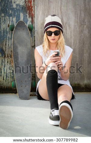 Pretty blond skater girl text messaging listening to music - stock photo