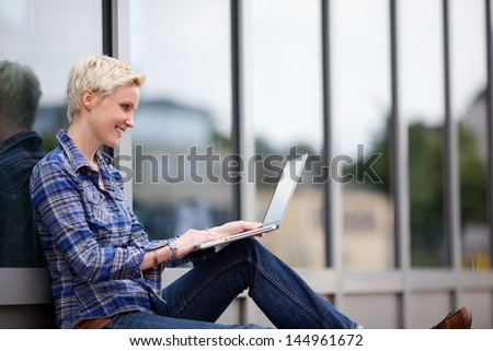 Pretty blond student using her laptop in the city sitting leaning against a glass storefront while sitting on the sidewalk - stock photo