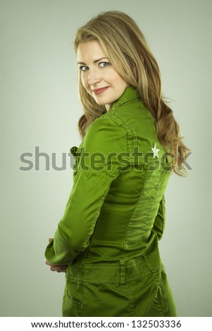 pretty blond wearing green dress on light background - stock photo