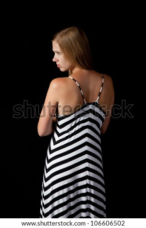 Pretty blond with her back to the camera, looking sideways over her left shoulder, and a black background - stock photo