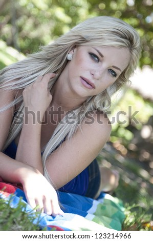 Pretty blond woman at a park. - stock photo