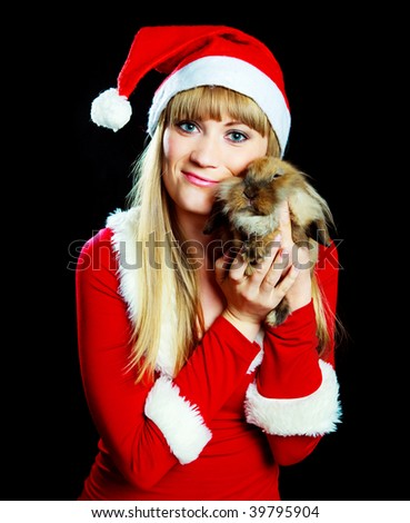 pretty blond woman dressed as Santa with a rabbit wearing a Santa's hat in her hands