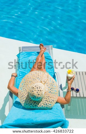 Pretty blond woman  enjoying a cocktail at the  swimming pool - stock photo