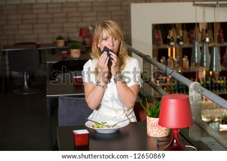 Pretty blond woman finishing her lunch in the cafetaria and wiping her mouth with a napkin - stock photo