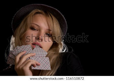 pretty blond woman in hat biting poker cards on black background - stock photo