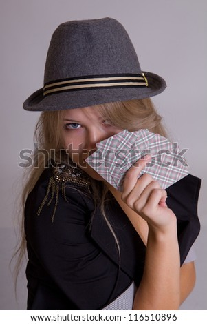 pretty blond woman in hat with playing cards - stock photo