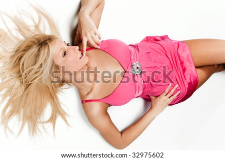 pretty blond woman in pink dress laying, studio white background - stock photo