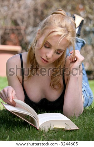pretty blond woman reading book in a park