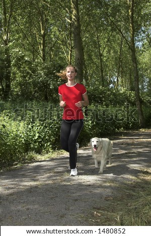 Pretty blond woman running in the woods with her dog - stock photo