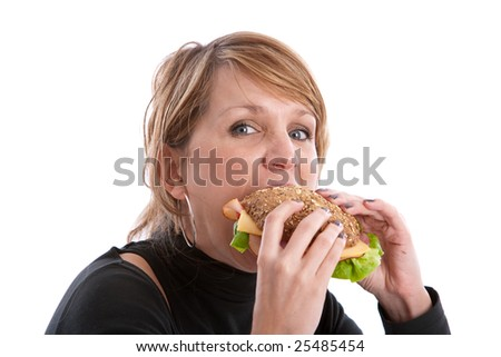 Pretty blond woman taking a big bite out of a healthy sandwich