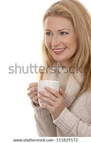 pretty blond woman wearing beige sweather drinking coffee