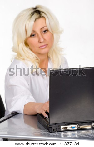 Pretty blond woman working on laptop. Isolated - stock photo