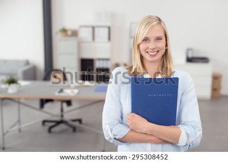 Pretty Blond Young Office Woman Hugging a Blue Documents Folder and Smiling at the Camera Inside the Office. - stock photo