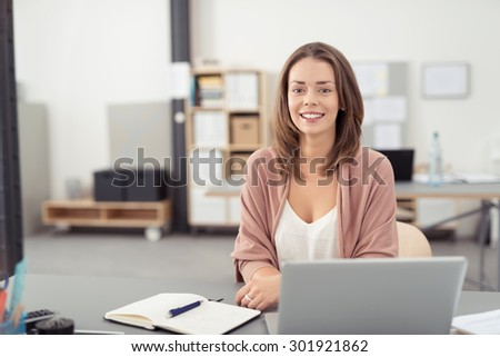 Pretty Blond Young Office Woman Sitting at her Desk with Notes and Laptop, Smiling at the Camera - stock photo