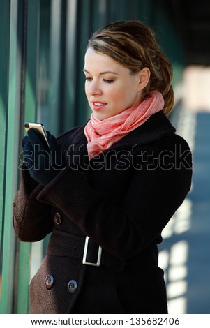 Pretty Blond Young Woman Texting On A Smartphone Mobile - stock photo