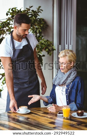 Pretty blonde arguing with the waiter at the cafe - stock photo