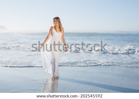 Pretty blonde at the beach in white sundress on a sunny day - stock photo