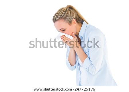 Pretty blonde blowing nose on tissue on white bakcground - stock photo