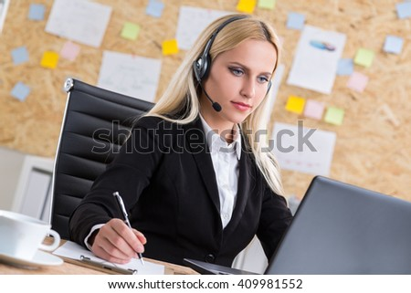 Pretty blonde call center operator looking at computer screen in office - stock photo