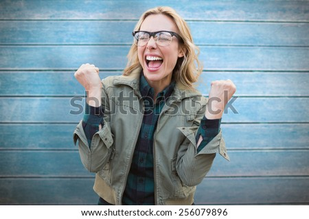 Pretty blonde cheering against wooden planks - stock photo