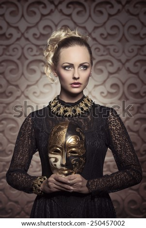 pretty blonde female posing in carnival shot with antique gothic lace dress, baroque jewellery and precious mask in the hands  - stock photo