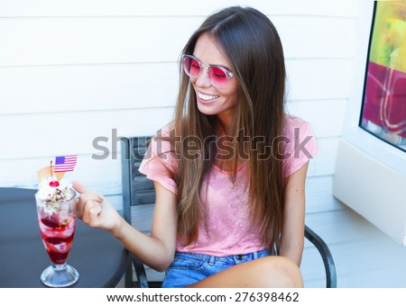 Pretty blonde girl eating ice cream. Indoor lifestyle portrait of woman in summer sunglasses.White background.Eating big strawberry ice cream with american flag.Summer hot days with ice cream.