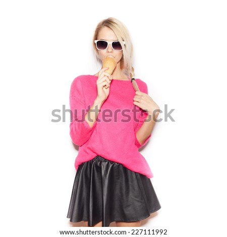 Pretty blonde girl eating ice cream. Indoor lifestyle portrait of woman in sunglasses.  White background, not isolated - stock photo