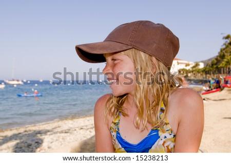 Pretty Blonde Girl in Ball Cap on a Gorgeous Beach. - stock photo