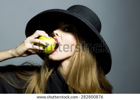 Pretty blonde girl in retro black hat with bright make up biting fresh green apple standing on gray background copyspace, horizontal picture - stock photo