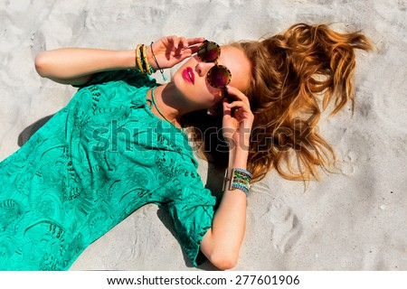 Pretty blonde girl lying on the tropical  sunny beach . Wearing cool stylish sunglasses, color    boho tunic and bright trendy accessories . Warm colors. - stock photo