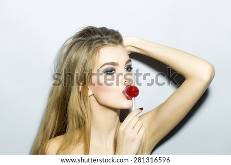 Pretty blonde girl portrait with bright make up looking away holding and licking round red sugar candy standing on light gray background copyspace, horizontal picture - stock photo