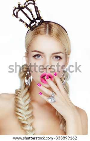 Pretty blonde girl posing in studio with a crown on his head. Nude makeup, pink lips and nails. - stock photo