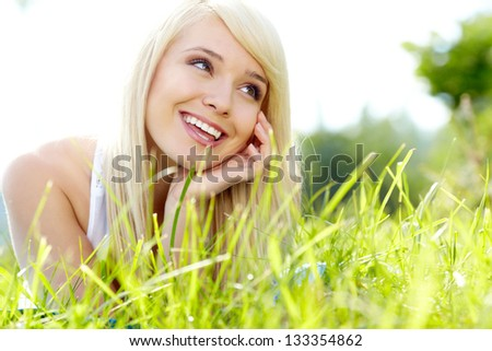 Pretty blonde girl relaxing outdoor in green grass - stock photo