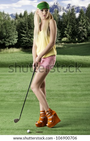 pretty blonde girl's playng golf with golf club, pink shorts and green sunshade, her body is turned of three quarters at right and she looks at left - stock photo