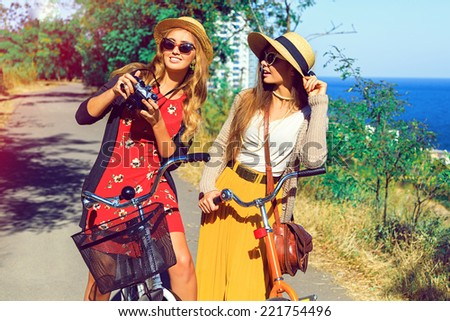 Pretty blonde girl showing pictures from her retro vintage hipster camera to her best friend, have nice day together walking with bicycles in the park near sea side. - stock photo