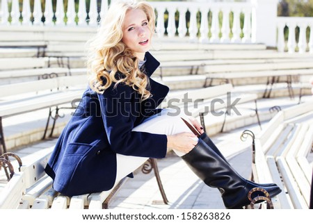 Pretty blonde girl sitting in the bench wearing in  coat - stock photo