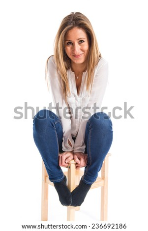 Pretty blonde girl sitting on chair - stock photo